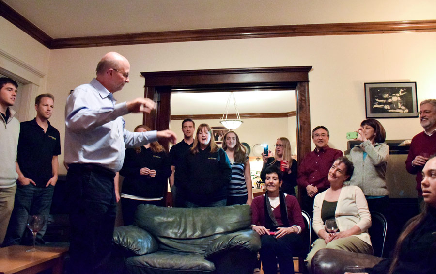 Jo-Michael Scheibe leads the Chamber Singers in an impromptu performance during a party hosted by the parents of student Antona Yost, a native of Salt Lake City.