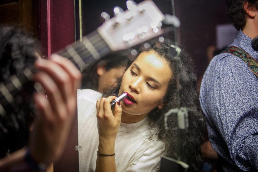 "Camila Mora, a junior vocalist, applies lipstick in the Troubadour ""green room"" (its walls are actually purple). (USC Photo/David Sprague)"
