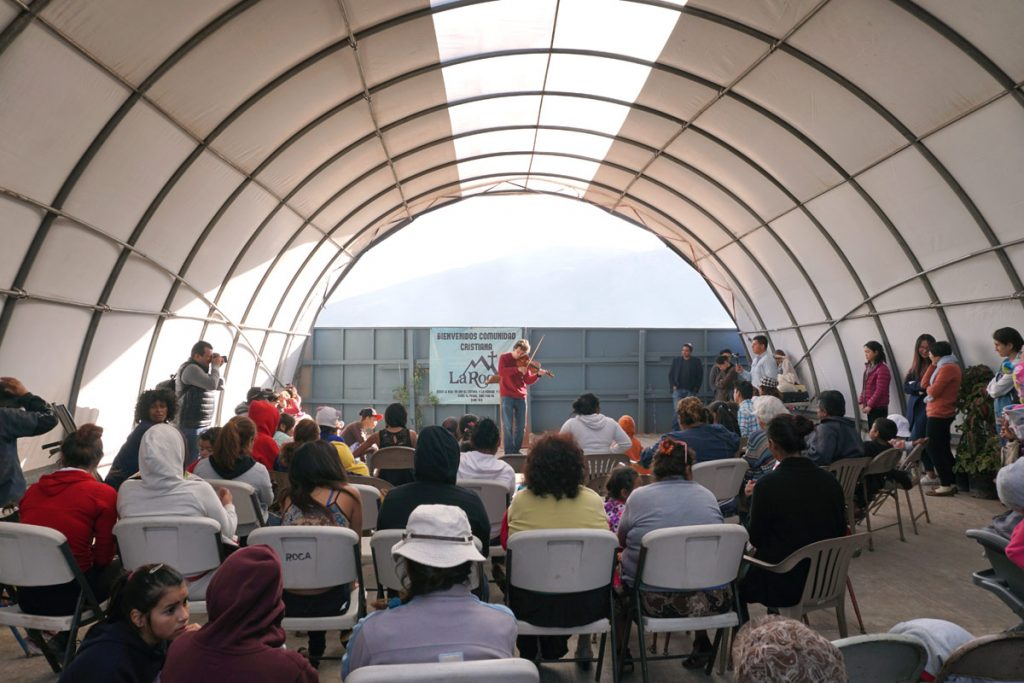 Master's student Orest Smouzh performs in a community church outside of a dump in Tijuana. (Photo by Moises Encino)