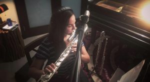Gina Luciani in home studio playing flute