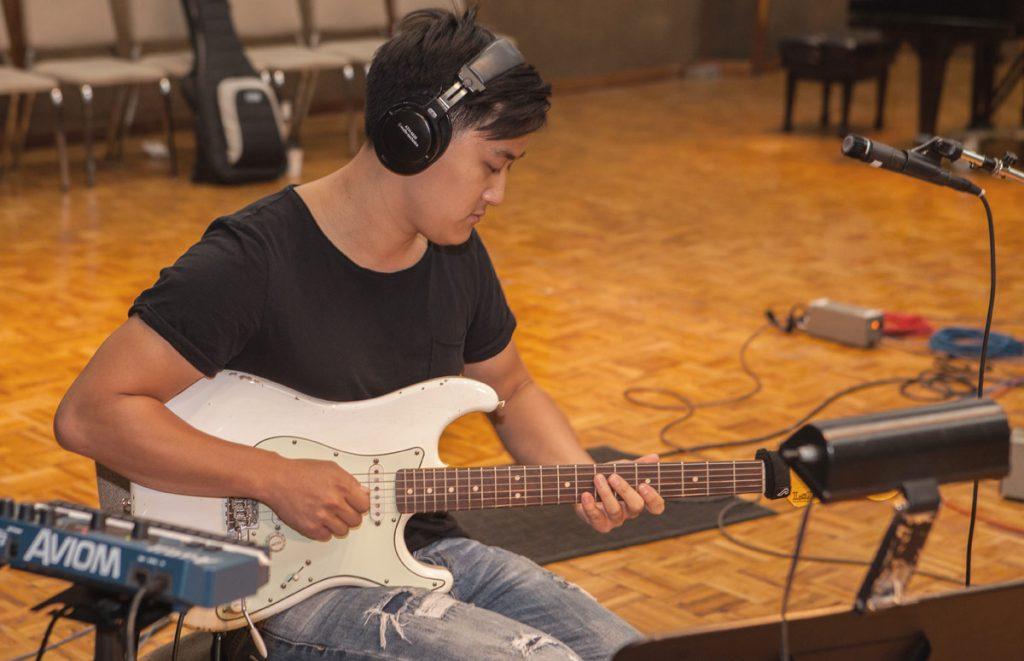 Sam Yun plays the guitar.