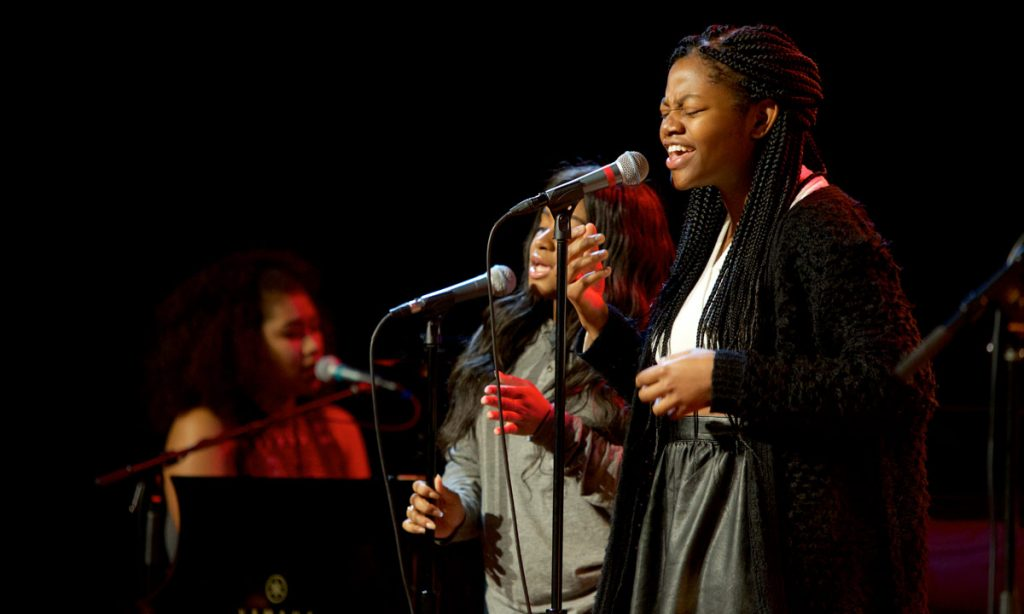 A band featuring, (R-L) vocalists Ashley Estes, Tehillah Alphonso, and keyboards/vocalist Alexa Angulo, performed for Jean.