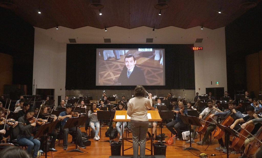 An L.A. Film Conducting Intensive fellow conducts an orchestra featuring USC Thornton students on the Eastwood Stage of Warner Bros Studios.
