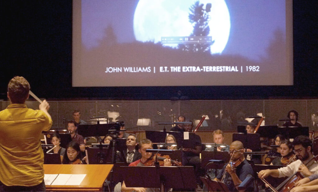 "A conducting fellow leads the orchestra in excerpts from John Williams' 1982 score to ""E.T. the Extra-Terrestrial."""