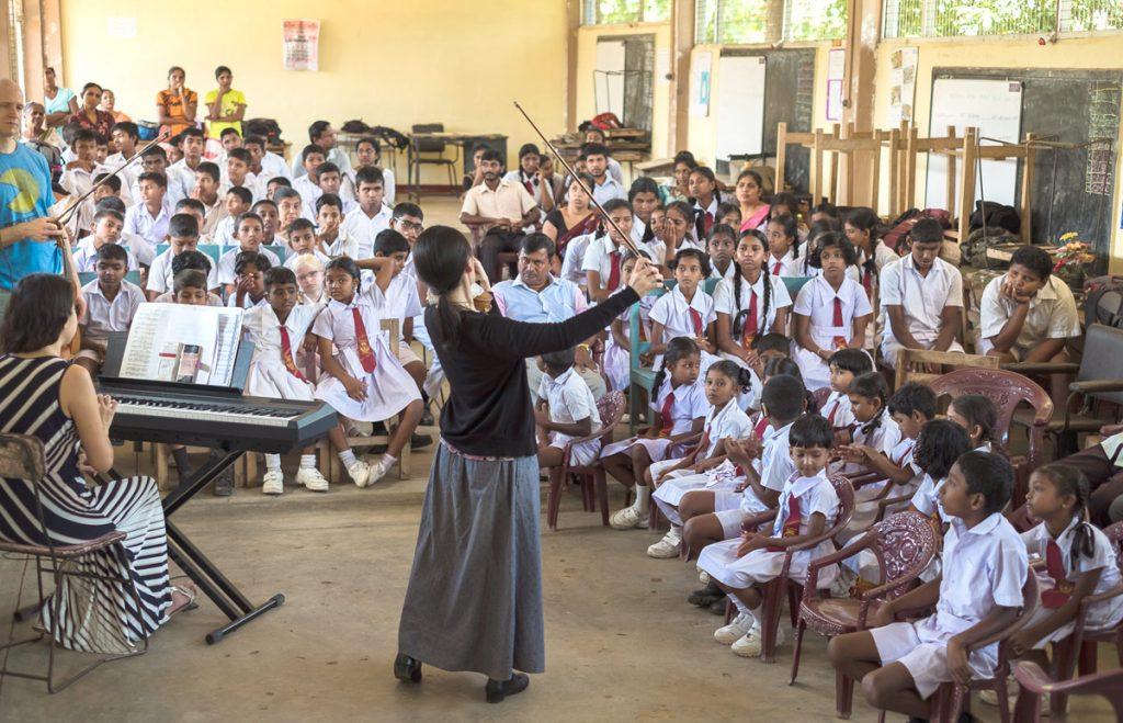 Midori performs for a group of school Sri Lankan school children with pianist Jiayi Shi.