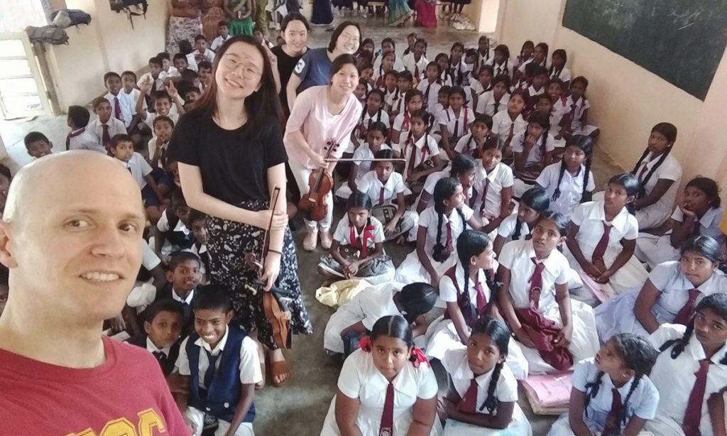 Thornton violinists Moni Simeonov, Yue Qian, Mei Ching Huang, Yabing Tan, and Chang He pose for a selfie with local children. (Photo courtesy of Moni Simeonov)
