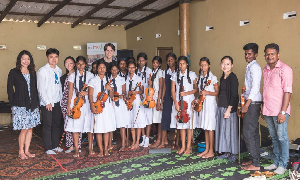 Midori Goto (third from right) and student musicians pose with young Sri Lankan music students.