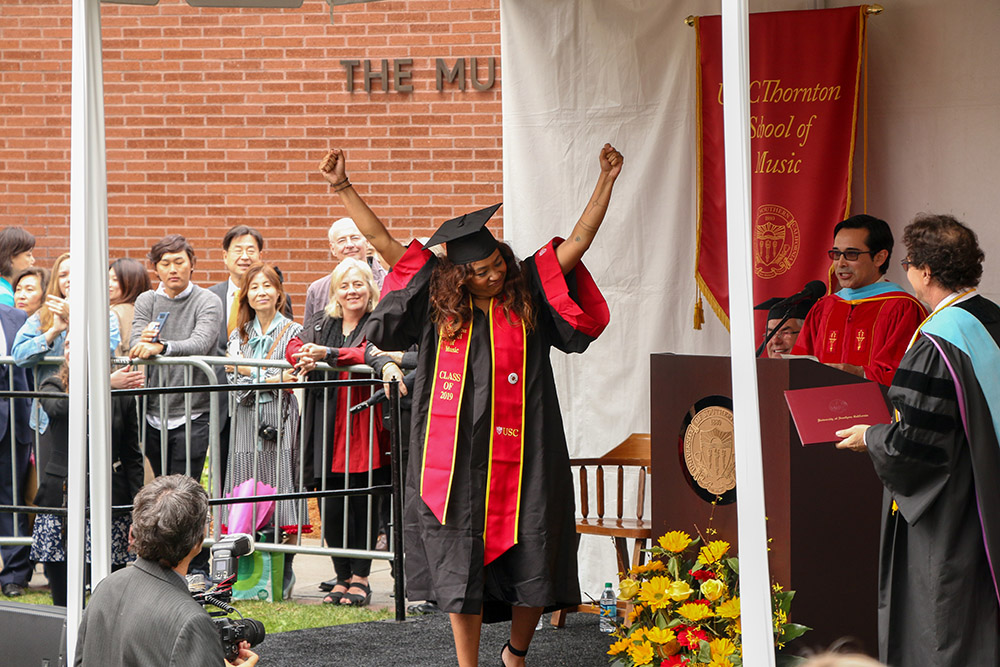 A 2019 USC Thornton graduate celebrates on stage.