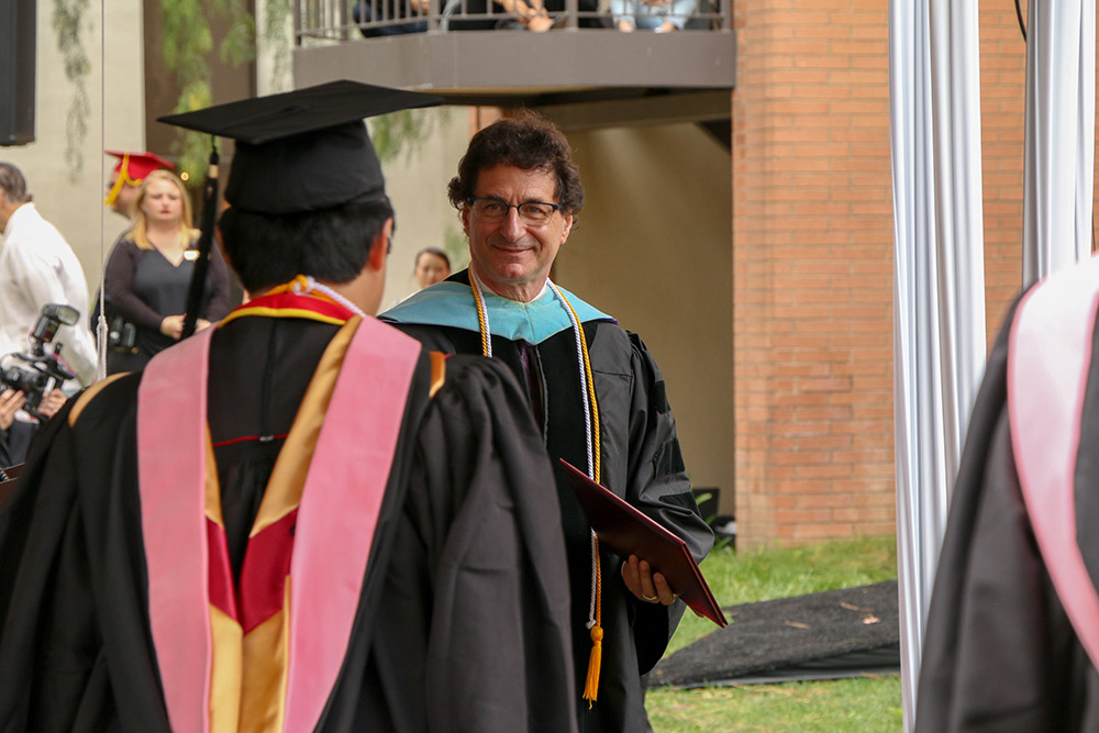 Dean Cutietta prepares to shake the hand of a Thornton graduate.