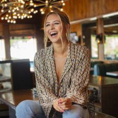 Carly Rose sitting on table in a diner and laughing
