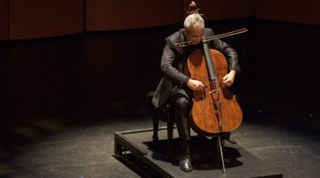 Photo of cellist on stage under spotlight