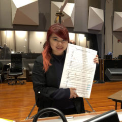 Photo of Jaimie Pangan in studio, holding up score