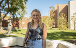 Portrait of Molly Sibley holding skateboard on campus