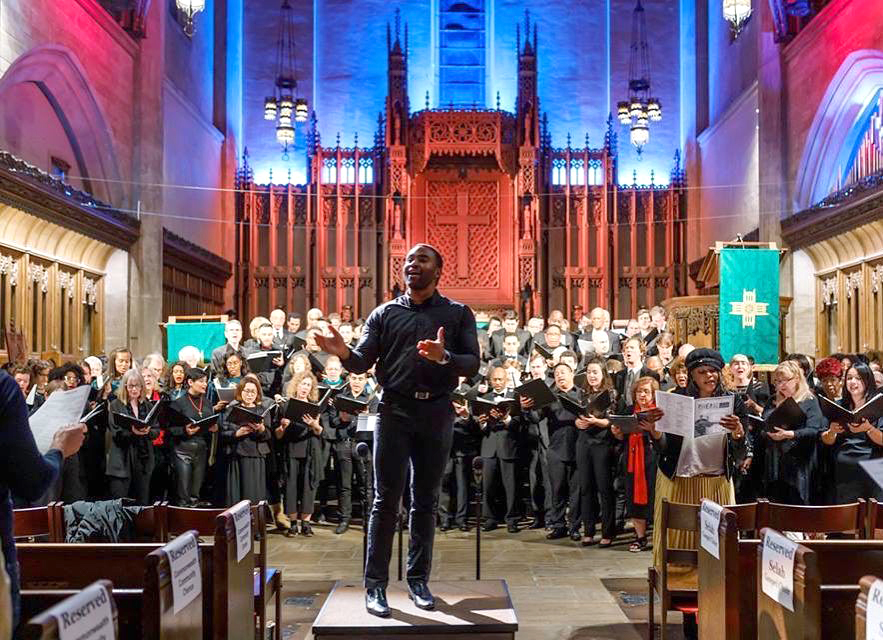 Photo of Alex Blake conducting in a church