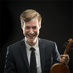 Photo of Jason Issokson holding violin