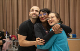 Three cast members embrace while rehearsing opera
