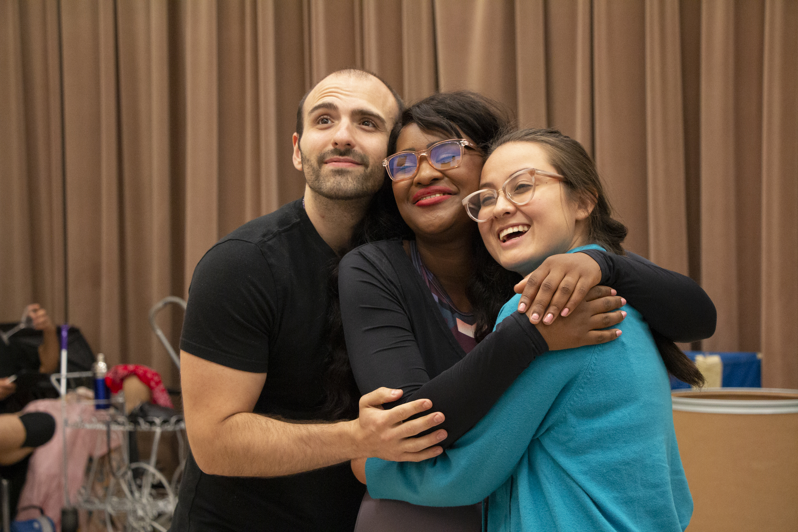 Three cast members embrace while rehearsing opera