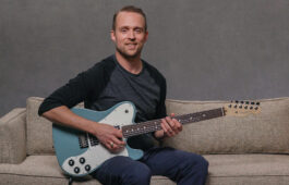Matt Lake pictured on sofa with guitar