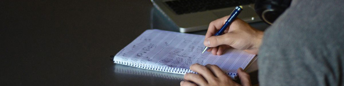 Photo of composer writing in notebook