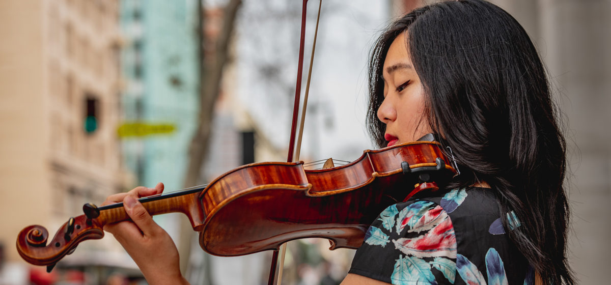 Photo of female student playing violin outdoors