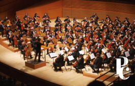 Photo of mass cello ensemble in Disney Hall with white logo