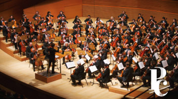 Photo of mass cello ensemble in Disney Hall with white logo