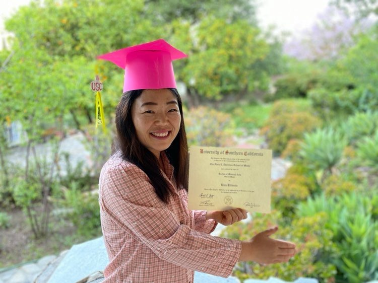 Rina Ritivoiu (DMA '19) graduated in the fall, and celebrates at home with her diploma and a homemade graduation cap