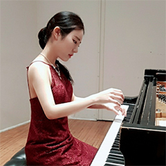 Doyoung Park seated at piano in formal attire