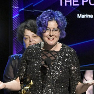 Nadia Schpachenko in black dress at microphone accepting award