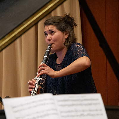 Woman playing clarinet, viewed through open lid of a piano
