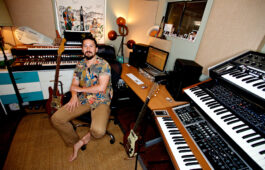 Mitchell Yoshida pictured in his home studio sitting on a chair surrounded by keyboards, guitars and recording equipment