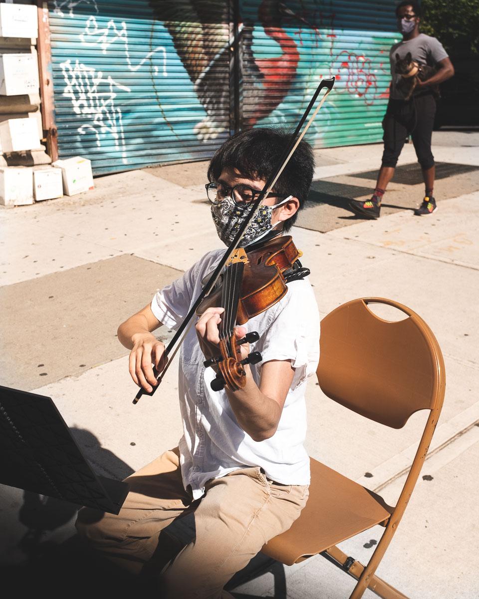 Jay Julio Laureta playing viola outdoors wearing a face mask