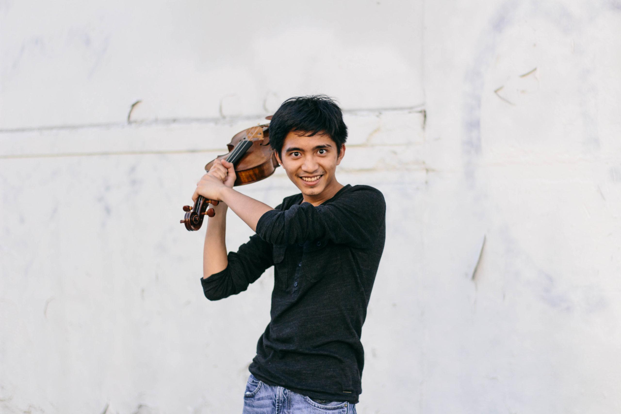 Jay Julio Laureta in a black shirt holding a viola over their shoulder