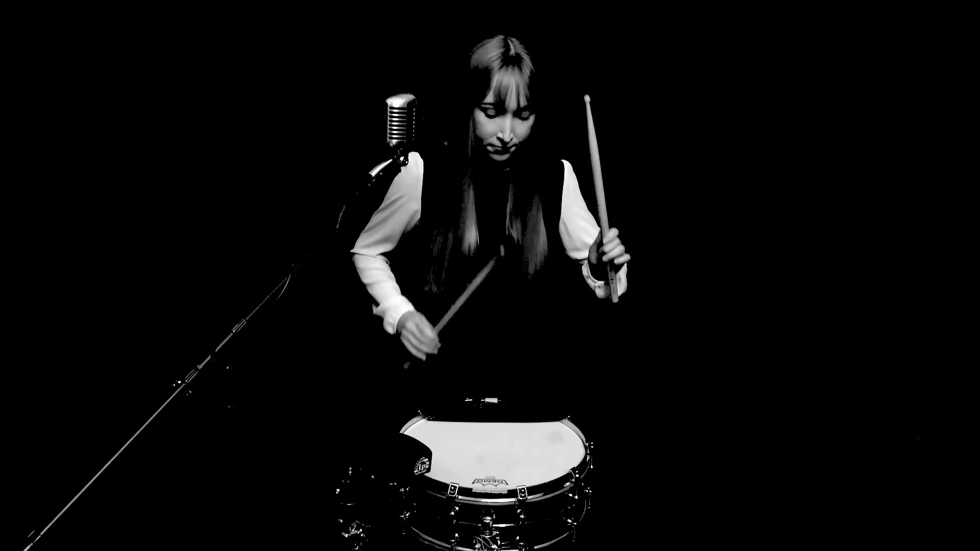Black and white image of a woman in performance black playing a snare drum