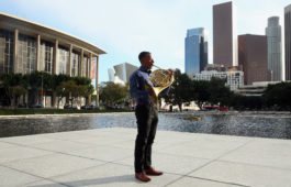 Malik Taylor stands in downtown LA holding french horn