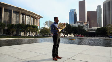 Man stands in downtown LA holding french horn