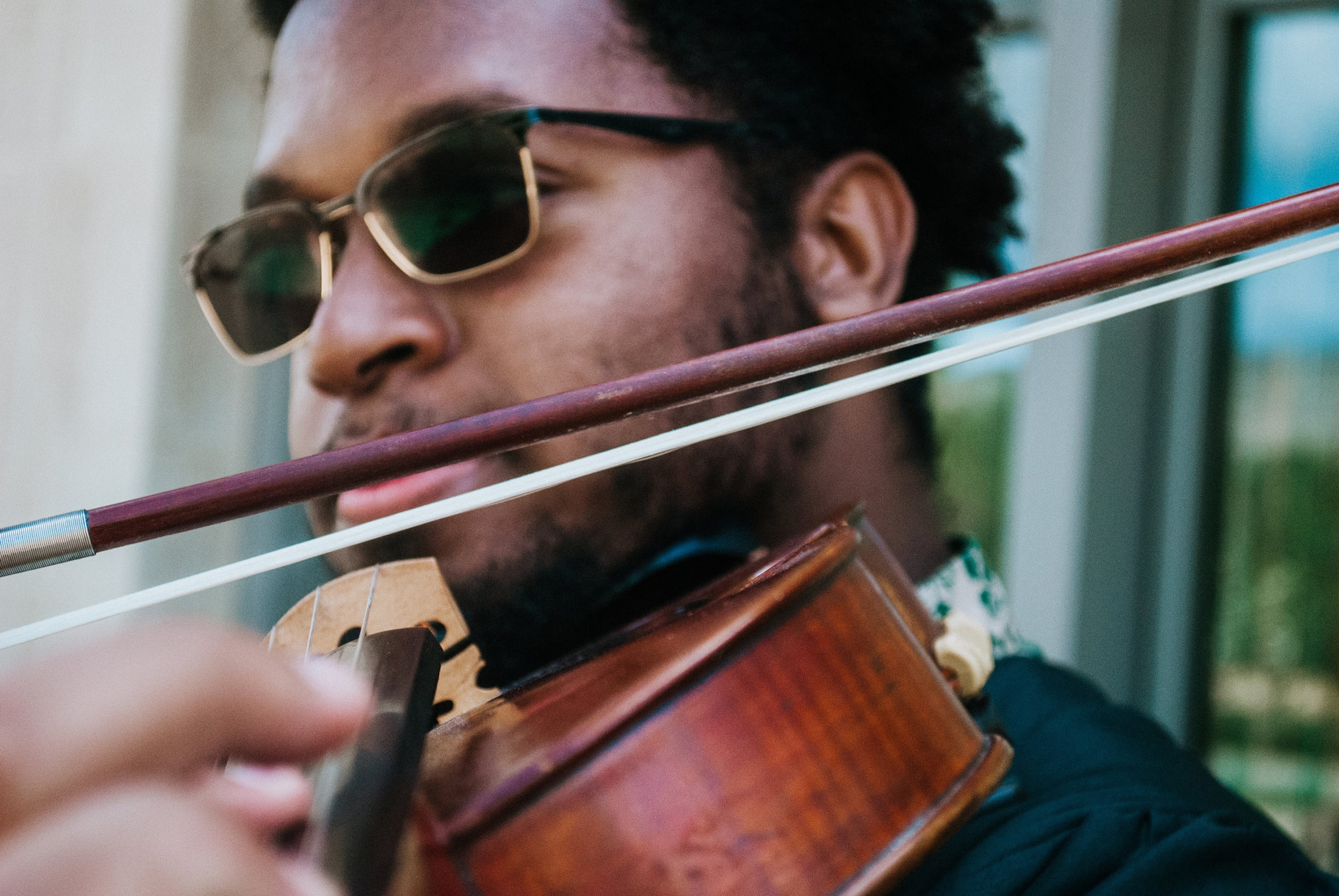 Wilfred pictured close up, playing the viola, with sunglasses on