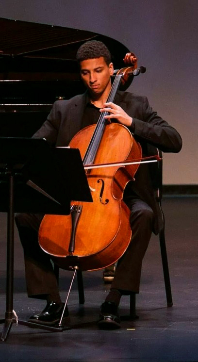 Myles Yeazell dressed in concert black playing cello on stage next to a piano