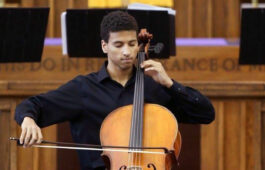 Myles Yeazell dressed in concert black playing the cello