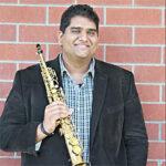 Andrew Harrison holding saxophone on brick background