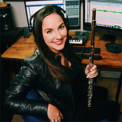 Gina Luciani holding flute with headphones on