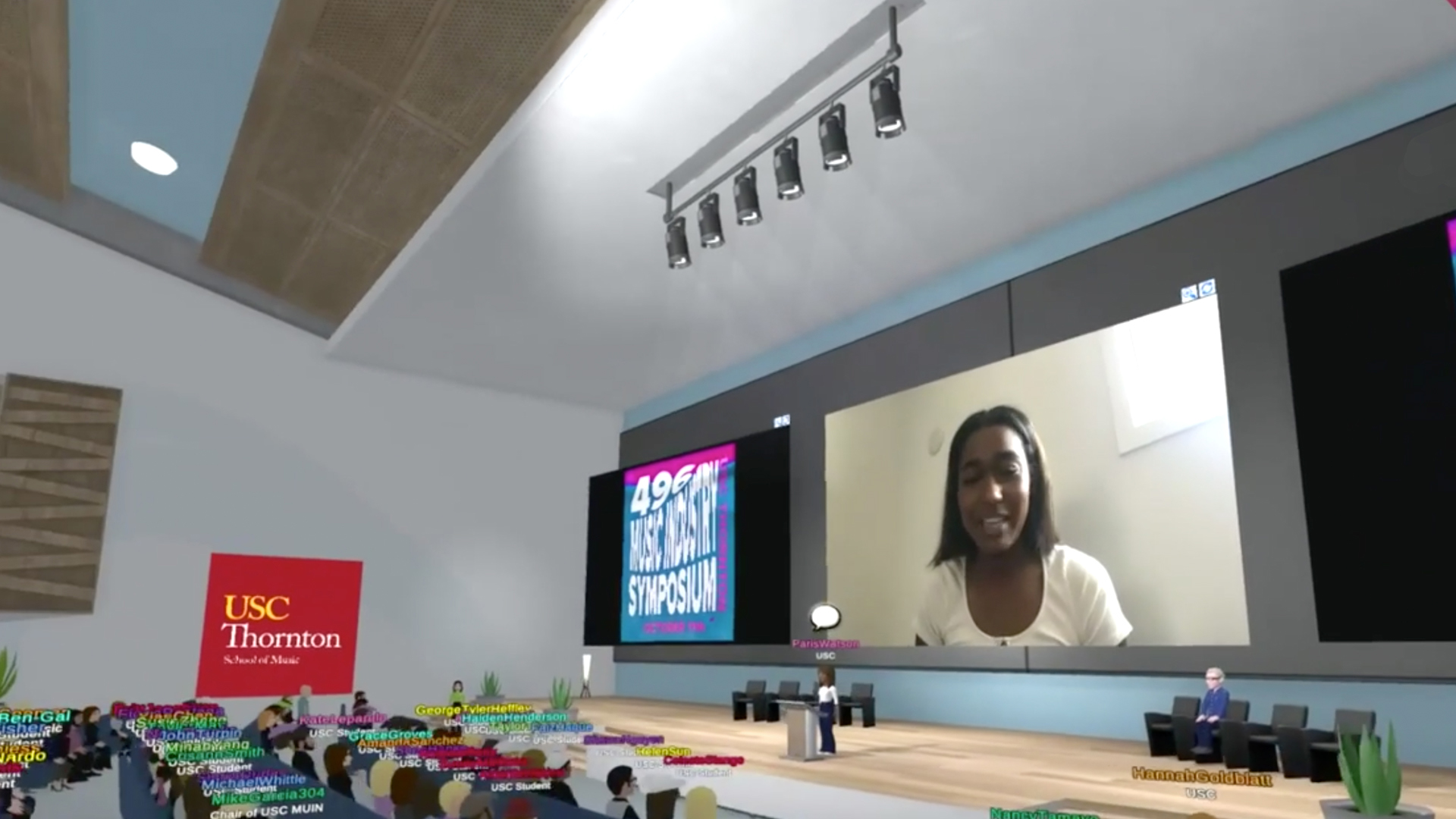 A view of an animated online classroom space, with a live video feed visible through an animated projector
