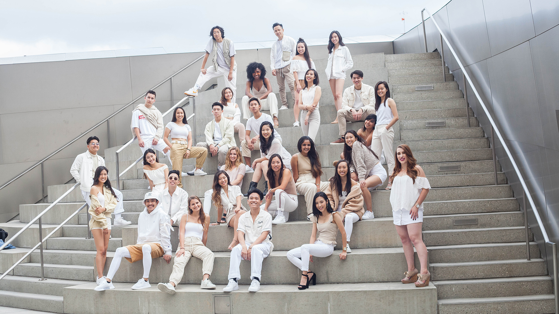 A group of dancers dressed in white standing on a sloping set of concrete stairs