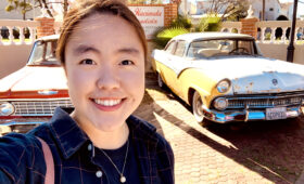 Linda Diaz standing beside classic cars
