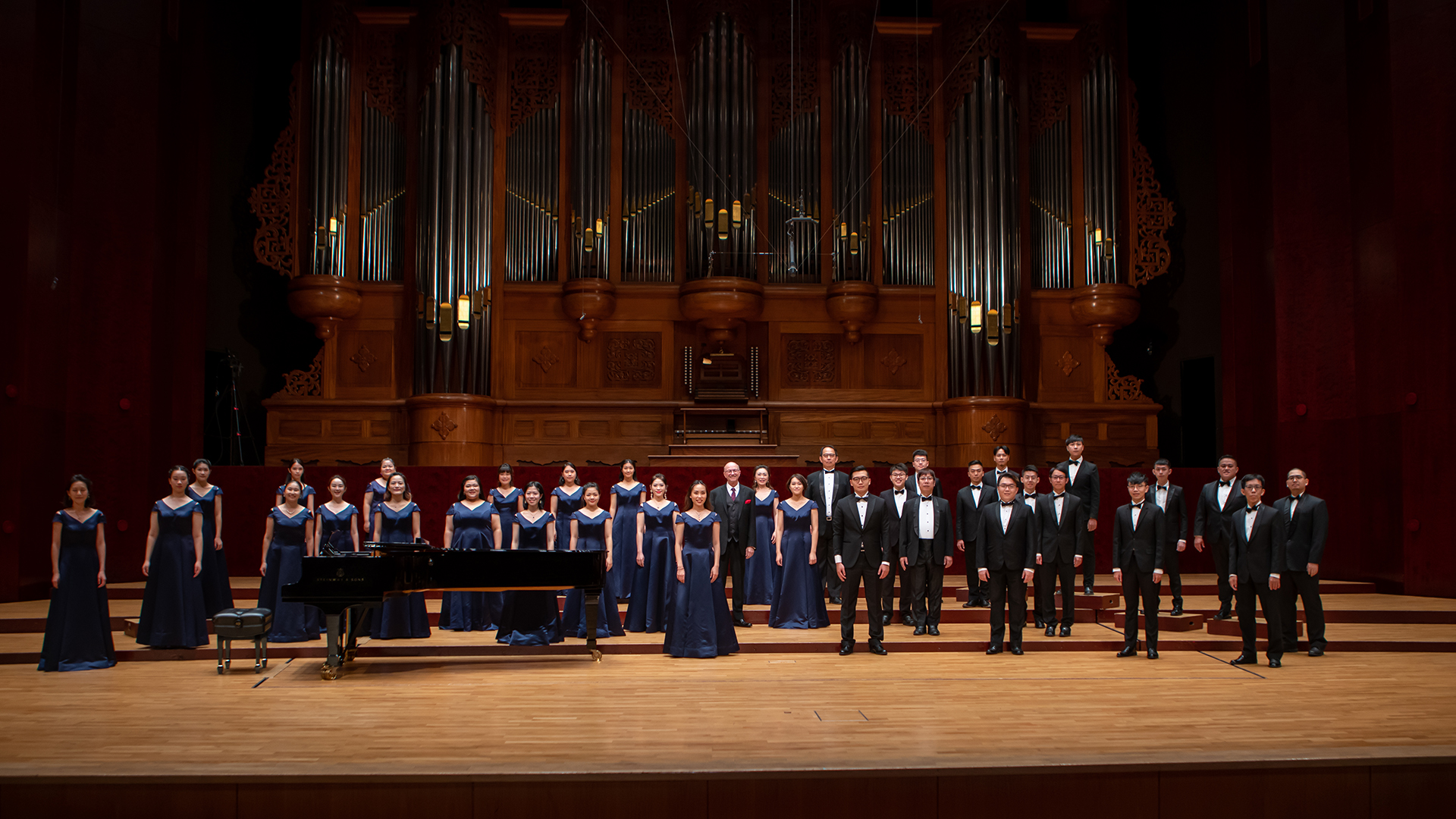 A choral ensemble stands on an ornate stage in formal attire