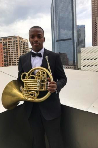 Malik Taylor, dressed in a tuxedo, stands on a roof in downtown LA holding his french horn