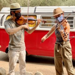 Photo of two violinists playing outdoors while wearing masks over their faces