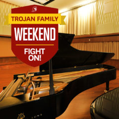 "Picture of a piano in Schoenfeld Hall with a logo reading ""Trojan Family Weekend - Fight on!"""