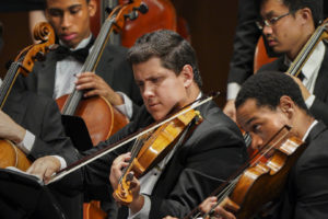 String musicians playing in an orchestra in formal attire