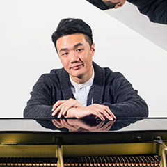 Barry Tan with arms on a piano, looking into the camera